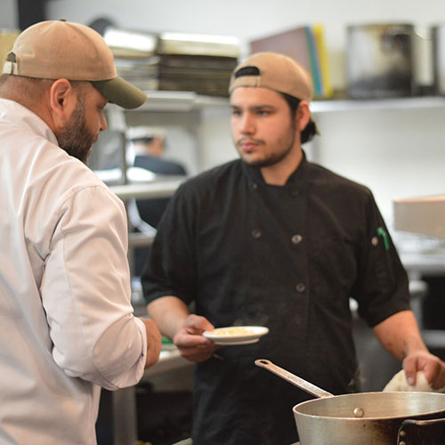 Chef Finkel giving directions to assistant in the kitchen